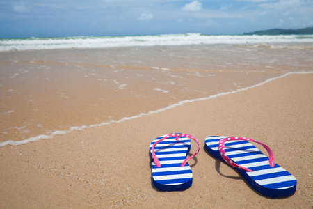 Colorful flipflop footware on sea beach  Holiday concept  photo