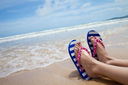 sandy feet: Young girl legs in colorful flipflop sandals on sea beach
