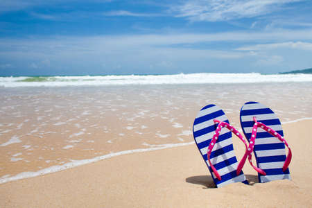 flip flops on the beach: Colorful flipflop pair on sea beach