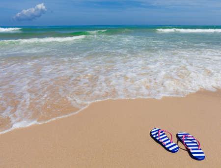 flops: Colorful striped sandals on sea beach Stock Photo