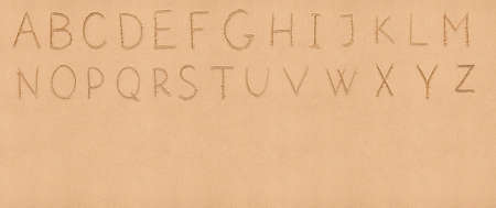 Handwriting English alphabet on flat sand with empty space appropriate as a background for your text photo