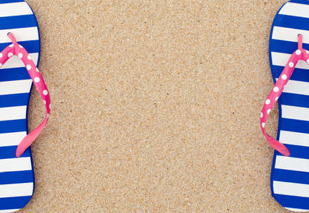 flip flops: Colorful flipflop pairas a frame on beach sand