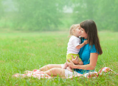 daughter kissing mother with love photo