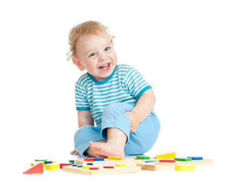 Adorable happy child playing educational toys isolated on white photo