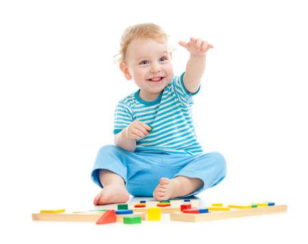 juguetes de madera: Feliz ni�o alegre que juega los juguetes educativos aislados en blanco