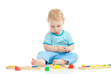 Serious pensive child playing logical education toys isolated on white photo