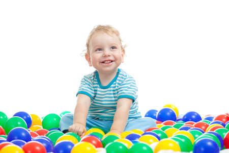 baby tooth: Cute boy playing colorful balls isolated on white Stock Photo
