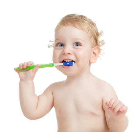 Happy child brushing teeth isolated on white photo