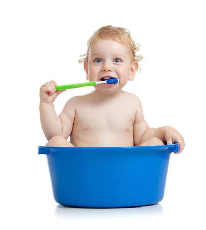 Happy baby kid brushing teeth sitting in basin