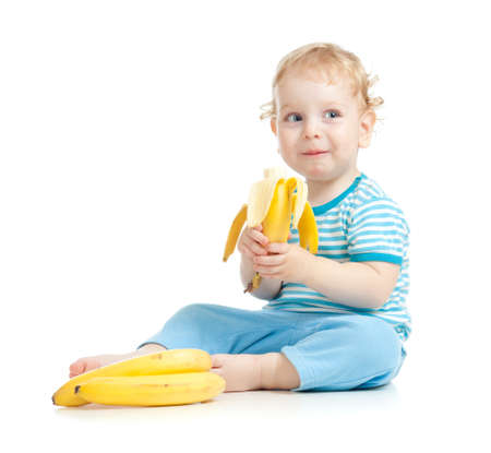 happy child eating healthy food fruits isolated on white photo