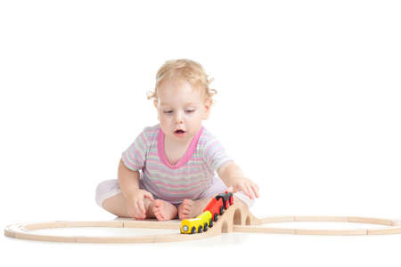 serious cute child is playing with wooden train isolated on white photo