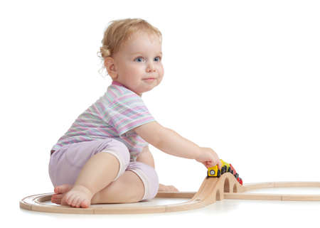 Cute child is playing with wooden train isolated on white photo