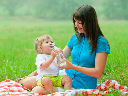 happy mother and daughter drinking clear water from bottle photo