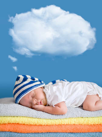Little baby sleeping on stack of colorful towels with a dreaming balloon above photo