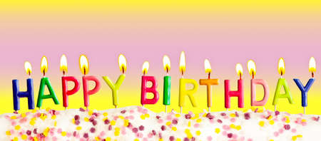 Happy birthday lit candles on colorful background photo