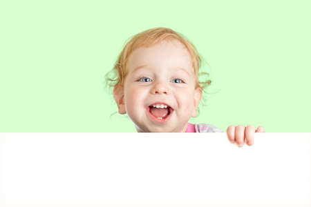 Happy child face behind blank advertising banner. Banner and green background are easily expandable in any direction. photo