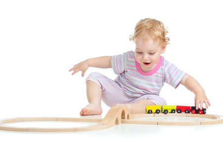 wood railroad: happy cute child playing with toy railroad isolated on white Stock Photo