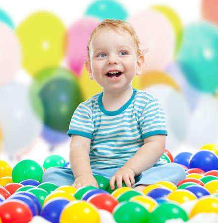 Cute boy playing colorful balls photo