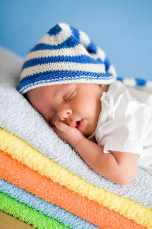 Sleeping newborn baby closeup portrait on colorful towels stack Stock Photo - 15199074