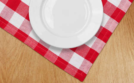 white plate on kitchen table with red checked tablecloth photo