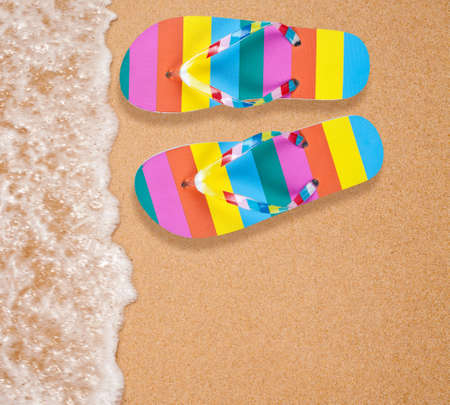 Colorful flipflop pair on sea beach photo