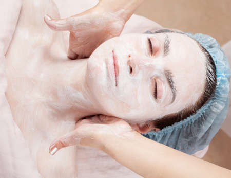 Beautiful woman with clear skin getting facial mask at salon photo