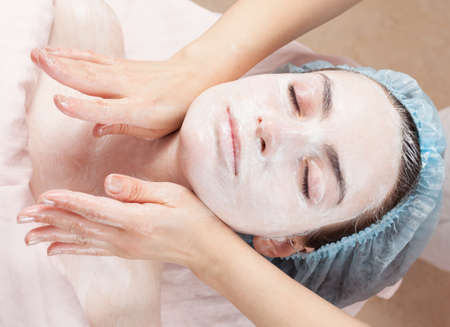 woman face cream: Beautiful woman with clear skin getting beauty treatment of her face at salon