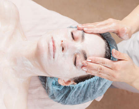 Beautiful woman with clear skin getting beauty treatment of her face at salon photo