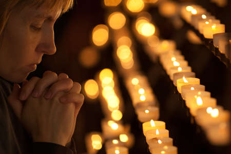 christian candle: Woman praying in Catholic church Stock Photo
