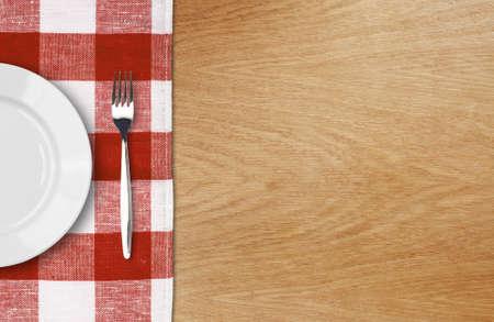 manteles: plato blanco y un tenedor en la mesa de madera con el mantel rojo comprobado y copyspace