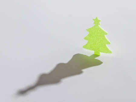 christmass: small green christmass tree with long shadow on white background