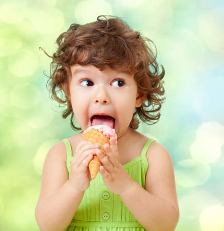 kids food: little curly girl with ice cream on colorful background