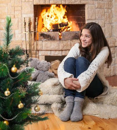 camino natale: felice adolescente in abiti invernali seduta caminetto