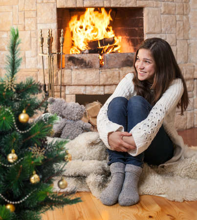 indoor: happy teenage girl in winter clothes sitting fireside