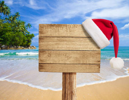 foam party: tropical beach wooden signboard with Christmas hat
