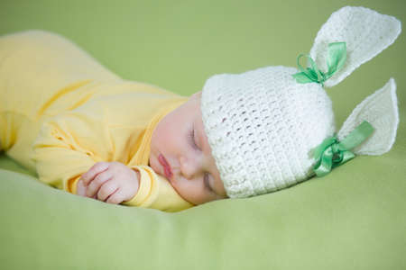 sleeping bunny baby in funny hat on green background photo