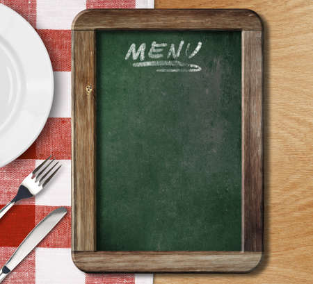 gingham: Menu blackboard lying on table with plate, knife and fork