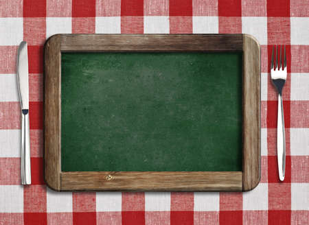 Menu blackboard lying on table with knife and fork photo
