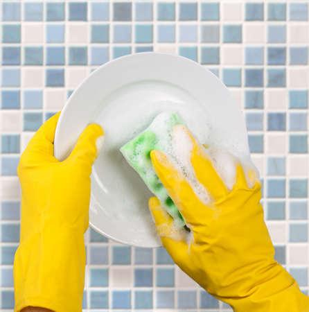 lavar trastes: Las manos en guantes amarillos lavado plato sobre fondo azulejo de la cocina