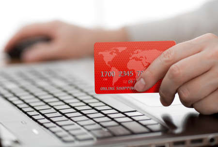 card payment: Man holding credit card in hand and entering security code using laptop keyboard