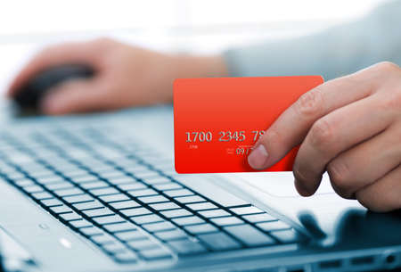 Man holding credit card in hand and entering security code using laptop keyboard Stock Photo - 15961737