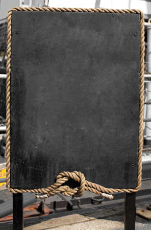 Grunge blackboard with rope frame outdoor as a background for your message photo