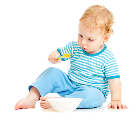 child or kid eating from plate with spoon photo