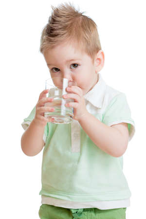 Little kid or child drinking water from glass isolated on white. It is a boy. Studio shot. photo
