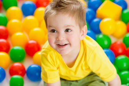 Lindo chico o niño que juega bolas de colores vista desde arriba
