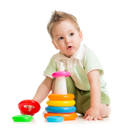 Cute kid playing colorful tower isolated on white photo