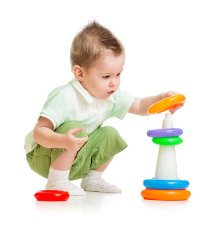 Cute child playing colorful tower isolated on white photo