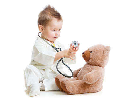 doctor toys: kid or child playing doctor with stethoscope and teddy bear isolated on white