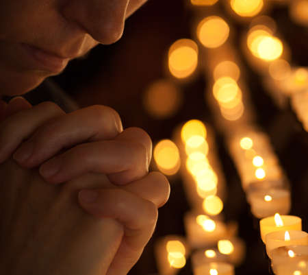 christian candle: Woman praying in church cropped part of face and hands closeup portrait Stock Photo