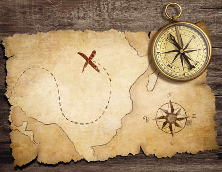 top of the world: aged brass antique nautical compass on table with old treasure map